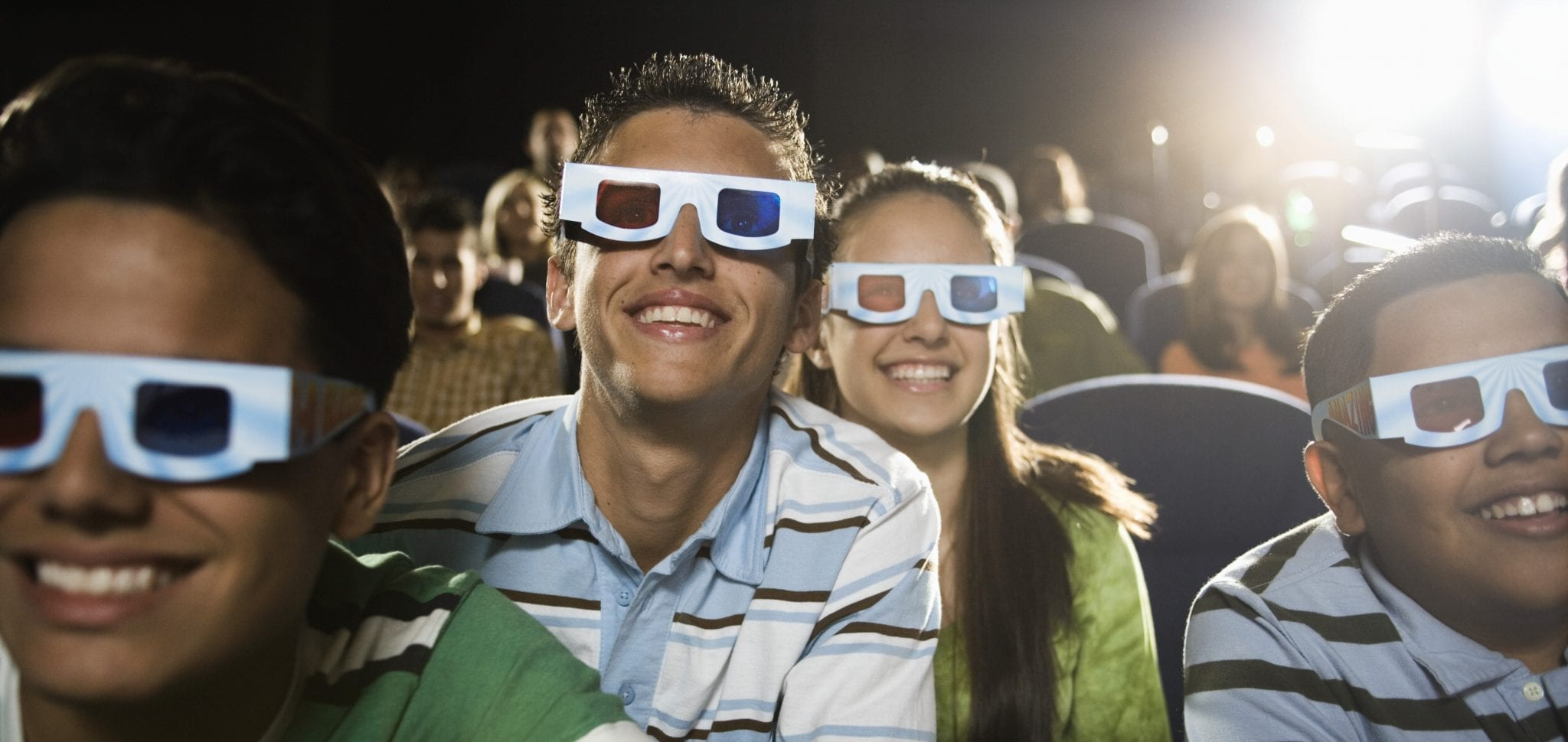 Movie ongoers are wearing 3D glasses & smiling